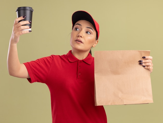 Junge lieferfrau in der roten uniform und in der kappe, die papierpaket hält, das kaffeetasse in der anderen hand mit ernstem gesicht steht, das über grüner wand steht