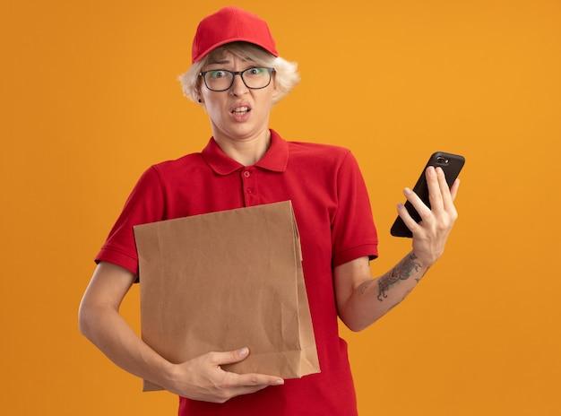 Junge lieferfrau in der roten uniform und in der kappe, die papierpaket und smartphone hält, verwirrt und sehr besorgt, über orange wand stehend
