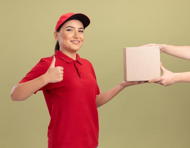 Junge lieferfrau in der roten uniform und in der kappe, die pappkarton zu einem kunden lächelnd freundlich zeigt daumen hoch stehend über grüner wand