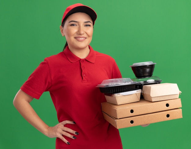 Junge lieferfrau in der roten uniform und in der kappe, die pizzakästen und nahrungsmittelpakete betrachten, die vorne lächelnd fröhlich über grüner wand stehend betrachten