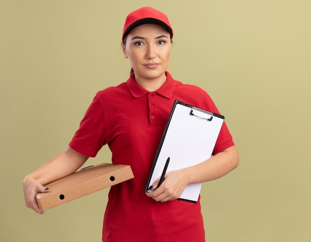 Junge lieferfrau in der roten uniform und in der kappe, die pizzaschachtel und zwischenablage mit balnk seiten hält, die vorne mit ernstem gesicht stehen, das über grüner wand steht