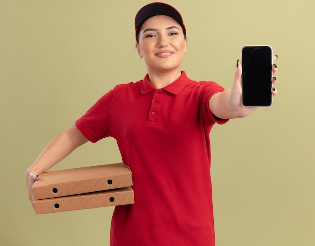 Junge lieferfrau in der roten uniform und in der kappe, die pizzaschachteln hält, die handy betrachten, das vorne lächelnd fröhlich über grüner wand steht