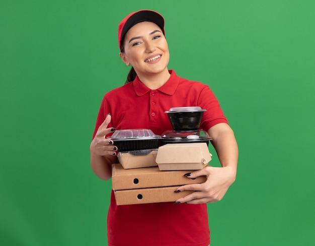 Junge lieferfrau in der roten uniform und in der kappe, die pizzaschachteln und nahrungsmittelpakete betrachten, die vorne mit lächeln auf gesicht stehen, das über grüner wand steht