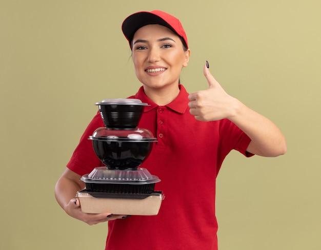 Junge lieferfrau in der roten uniform und in der kappe, die stapel von nahrungsmittelpaketen hält, die nach vorne lächelnd fröhlich zeigen, daumen hoch stehend über grüner wand