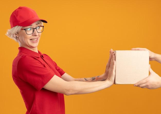 Junge lieferfrau in roter uniform und kappe, die sich weigert, kastenpaket zu nehmen, das über orange wand steht
