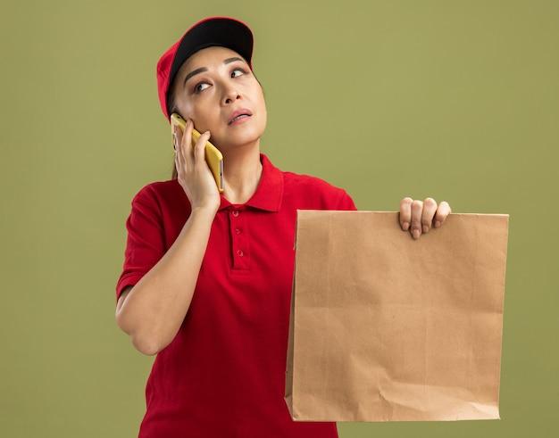 Junge lieferfrau in roter uniform und mütze, die ein papierpaket hält, das verwirrt aussieht, während sie auf dem handy über der grünen wand spricht