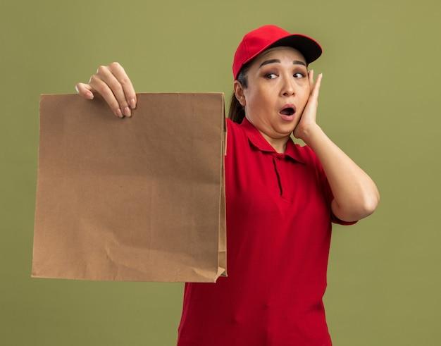 Junge lieferfrau in roter uniform und mütze, die ein papierpaket hält und es verwirrt und überrascht ansieht, als es über grüner wand steht?