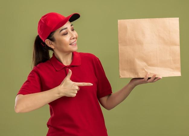 Junge lieferfrau in roter uniform und mütze, die ein papierpaket hält und mit dem zeigefinger darauf zeigt, lächelt selbstbewusst über grüner wand