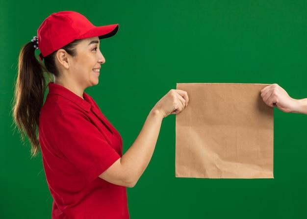 Junge lieferfrau in roter uniform und mütze, die einem kunden ein papierpaket gibt, der selbstbewusst über grüner wand steht?