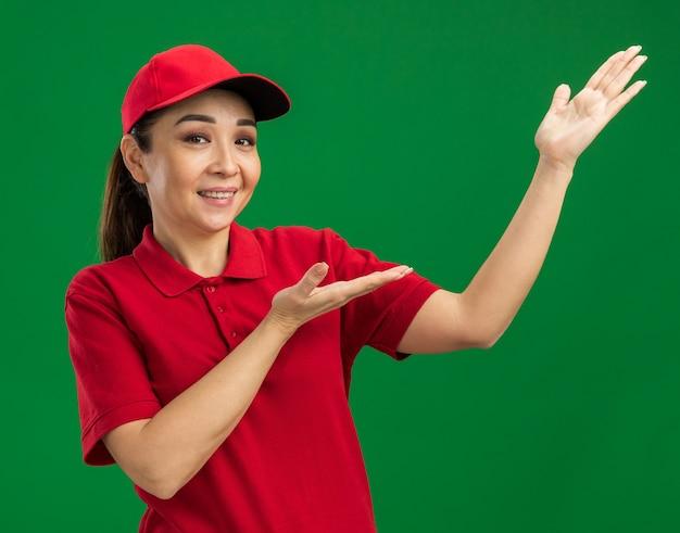 Junge lieferfrau in roter uniform und mütze, die kopienraum mit den armen der hände präsentiert, die glücklich und positiv lächeln