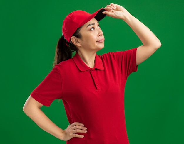Junge lieferfrau in roter uniform und mütze, die mit skeptischem ausdruck aufschaut