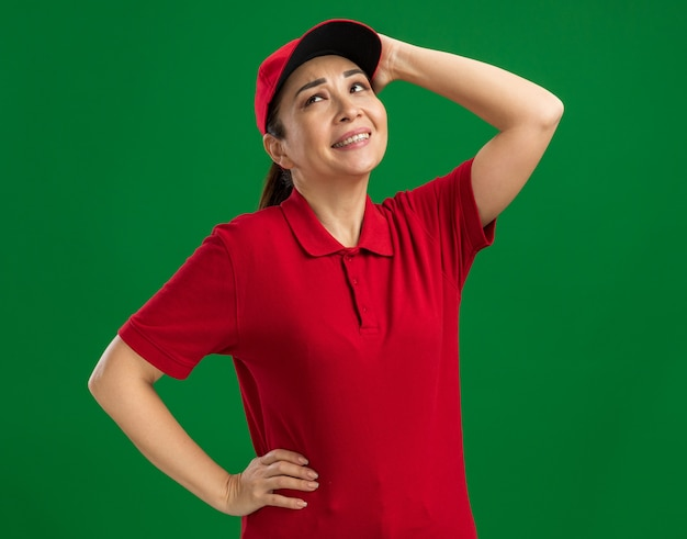 Junge lieferfrau in roter uniform und mütze, die mit verwirrtem ausdruck aufschaut und ihren kopf berührt, der über grüner wand steht?