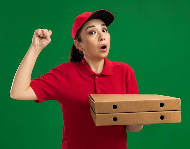 Junge lieferfrau in roter uniform und mütze, die pizzakartons hält und die faust hebt und überrascht über grüner wand steht