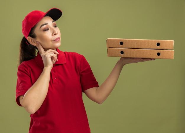 Junge lieferfrau in roter uniform und mütze, die pizzakartons hält und sie mit skeptischem gesichtsausdruck über grüner wand betrachtet