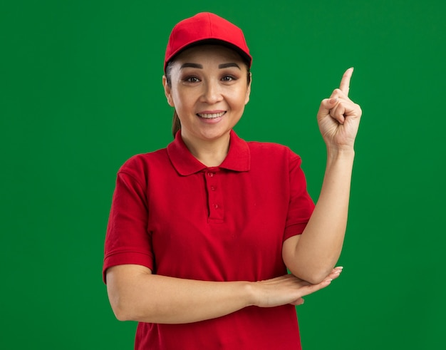 Junge lieferfrau in roter uniform und mütze glücklich und positiv, die den zeigefinger zeigt, der selbstbewusst über grüner wand steht