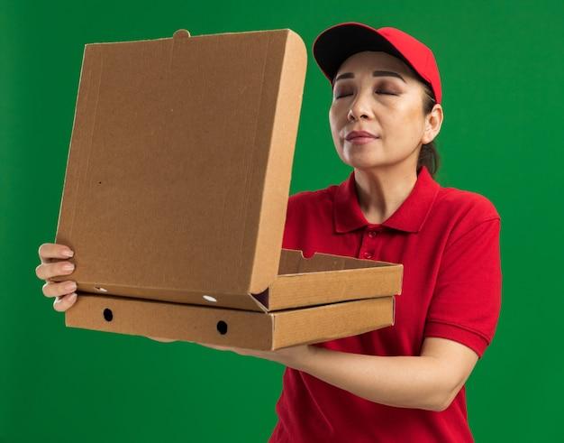 Junge lieferfrau in roter uniform und mütze mit pizzakartons, die angenehmes aroma einatmet, mit geschlossenen augen über grüner wand stehend