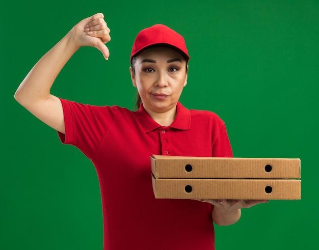 Junge lieferfrau in roter uniform und mütze mit pizzakartons ist unzufrieden und zeigt daumen nach unten über grüner wand stehend