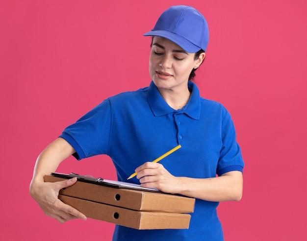 Junge lieferfrau in uniform und mütze, die pizzapakete hält und in die zwischenablage schreibt, mit bleistift isoliert auf rosa wand
