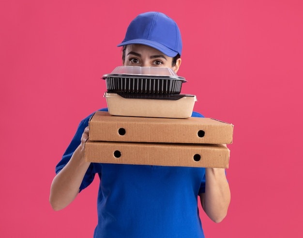 Junge lieferfrau in uniform und mütze, die pizzapakete mit papiernahrungspaket und lebensmittelbehälter auf ihnen hält, die von hinten von hinten einzeln auf rosa wand blicken