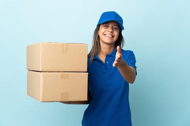 Junge lieferfrau isoliert auf blauen händeschütteln für das schließen eines guten geschäfts