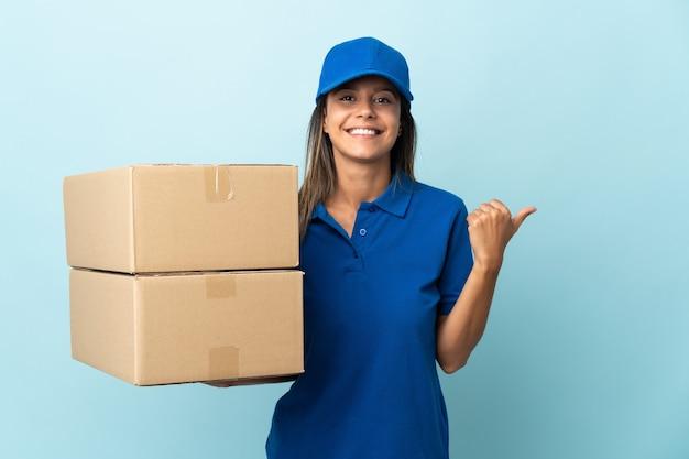 Junge lieferfrau lokalisiert auf blau, das zur seite zeigt, um ein produkt zu präsentieren