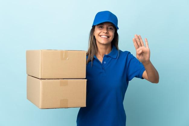 Junge lieferfrau lokalisiert auf blau glücklich und zählt vier mit den fingern