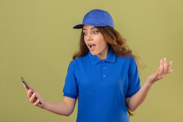 Junge lieferfrau mit dem gelockten haar, das blaues poloshirt und die kappe trägt, die bildschirm des smartphones überrascht mit hand über lokalisiertem grünem hintergrund überrascht betrachten