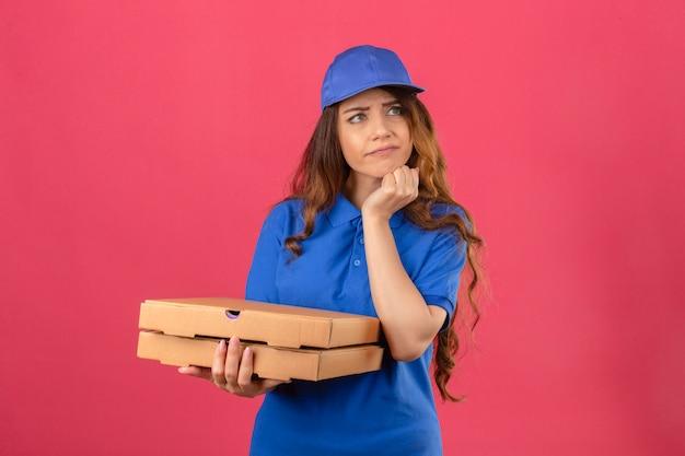 Junge lieferfrau mit dem gelockten haar, das blaues poloshirt und kappe steht, die mit pizzakästen stehen, die beiseite mit hand auf kinn denken, das zweifel über isoliertem rosa hintergrund hat