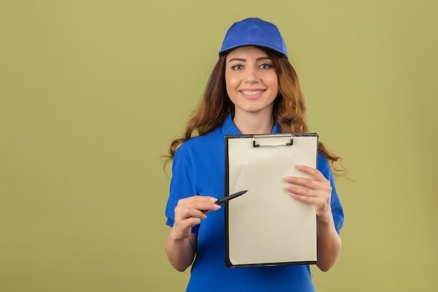 Junge lieferfrau mit dem gelockten haar, das blaues poloshirt und kappe trägt, die mit klemmbrett und stift stehen und nach einer unterschrift lächelnd freundlich betrachten kamera über lokalisiertem grünem hintergrund fragen