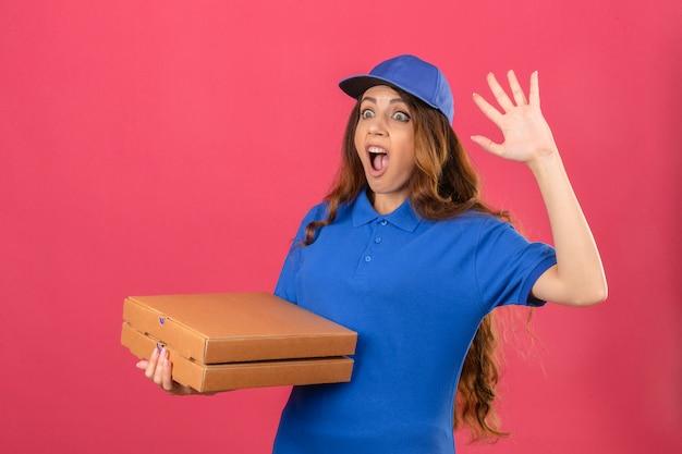 Junge lieferfrau mit dem lockigen haar, das blaues poloshirt und mütze trägt, die mit pizzakartons stehen, die schockiert ängstlichen oder besorgten mund weit offen mit der hand neben kopf über isoliertem rosa rücken suchen