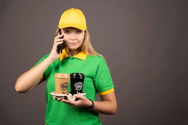 Junge lieferfrau mit den kaffeetassen, die auf smartphone sprechen. hochwertiges foto