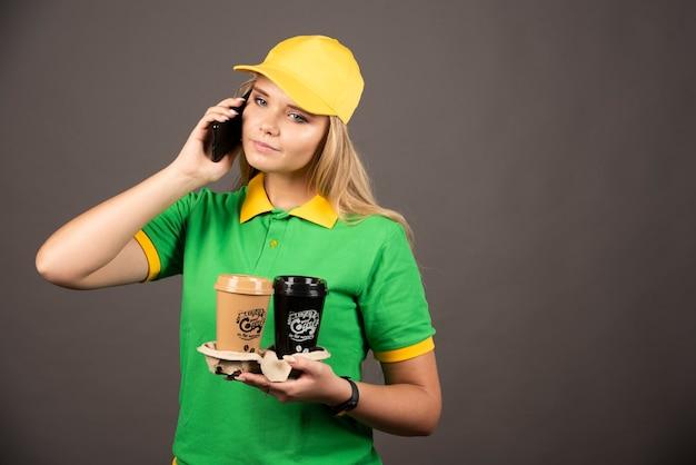 Junge lieferfrau mit den kaffeetassen, die auf smartphone sprechen.
