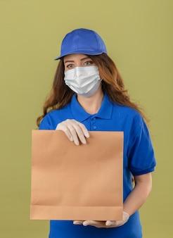 Junge lieferfrau mit lockigem haar, das blaues poloshirt und kappe in der medizinischen schutzmaske trägt, die mit papierpaket steht, das beiseite mit ernstem gesicht über lokalisiertem grünem hintergrund schaut