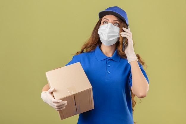 Junge lieferfrau mit lockigem haar, das blaues poloshirt und kappe in der medizinischen schutzmaske trägt, die mit pappkarton steht, der auf handy über lokalisiertem grünem hintergrund spricht