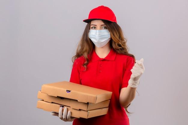 Junge lieferfrau mit lockigem haar, das rotes poloshirt und kappe in der medizinischen schutzmaske und in den handschuhen trägt, die mit pizzakästen stehen, die eine geldgeste tun, die über lokalisierten weißen hintergrund lächelt