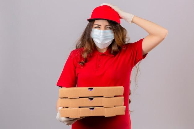 Junge lieferfrau mit lockigem haar, das rotes poloshirt und kappe in der medizinischen schutzmaske und in den handschuhen trägt, die mit pizzaschachteln mit hand auf kopf für fehler stehen, erinnern fehler über isoliertes weiß
