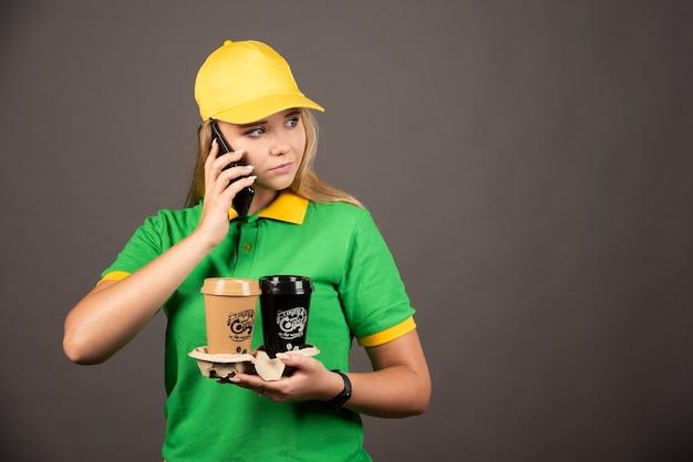 Junge lieferfrau mit tassen kaffee, die auf smartphone spricht.