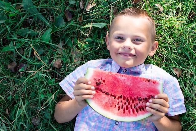 Junge liegt auf grünem gras und hält ein großes stück wassermelone, ein kleiner schüler isst eine wassermelone an einem sonnigen sommertag, kopienraum