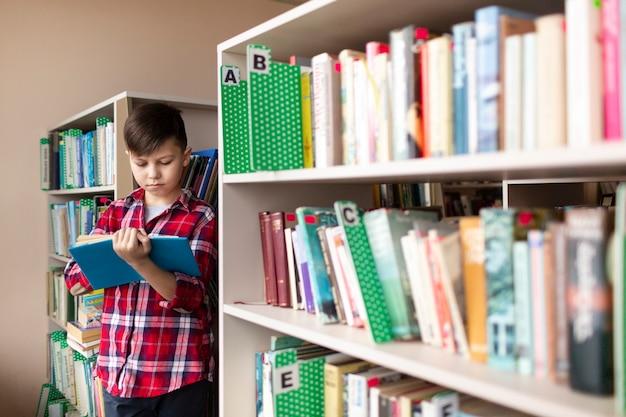 Junge liest zwischen regalen