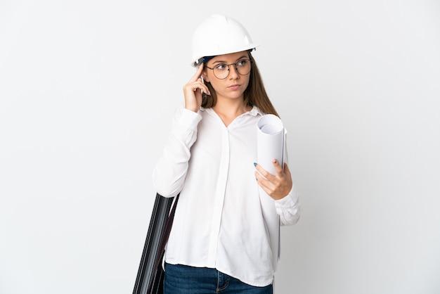 Junge litauische architektenfrau mit helm und halteplänen lokalisiert auf weißem hintergrund, der zweifel und denken hat