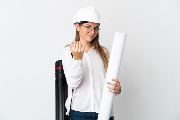 Junge litauische architektenfrau mit helm und halteplänen lokalisiert auf weißem hintergrund einladend, mit hand zu kommen. schön, dass du gekommen bist