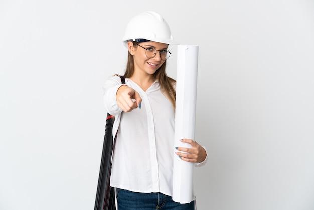 Junge litauische architektenfrau mit helm und halteplänen lokalisiert auf weißer wand, die front mit glücklichem ausdruck zeigt