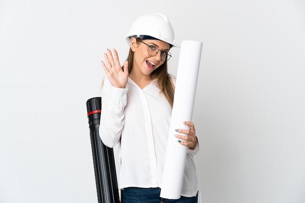 Junge litauische architektenfrau mit helm und halteplänen lokalisiert auf weißer wand, die mit hand mit glücklichem ausdruck salutiert