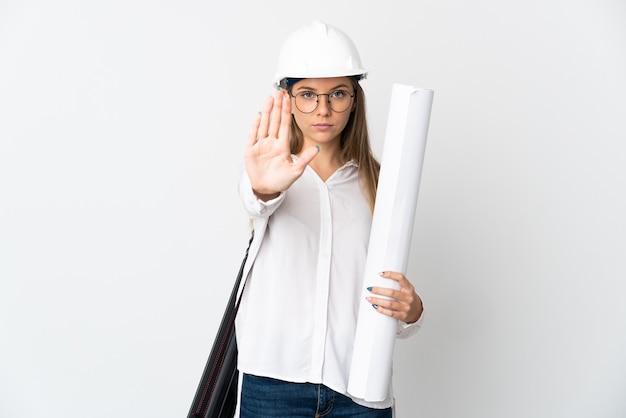 Junge litauische architektenfrau mit helm und halteplänen lokalisiert auf weißer wand, die stoppgeste macht