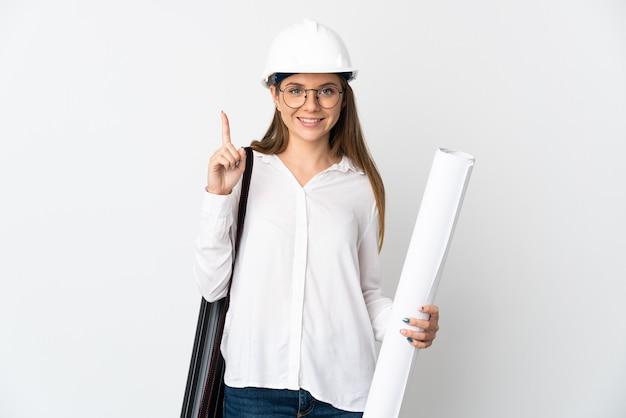 Junge litauische architektin mit helm und halteplänen lokalisiert auf weißem hintergrund, der eine große idee aufzeigt