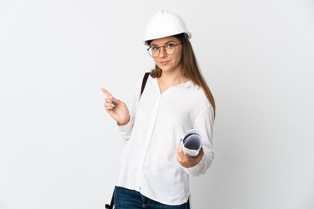 Junge litauische architektin mit helm und halteplänen lokalisiert auf weißem hintergrund, der finger zur seite zeigt