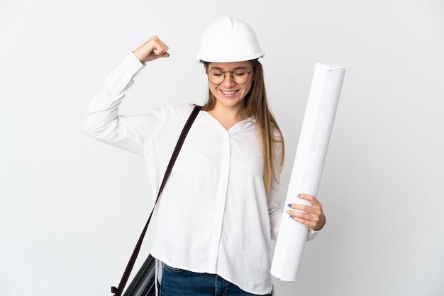 Junge litauische architektin mit helm und halteplänen lokalisiert auf weißer wand, die starke geste tut