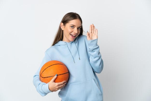 Junge litauische frau, die basketball spielt, lokalisiert auf weißer wand, die mit hand mit glücklichem ausdruck salutiert