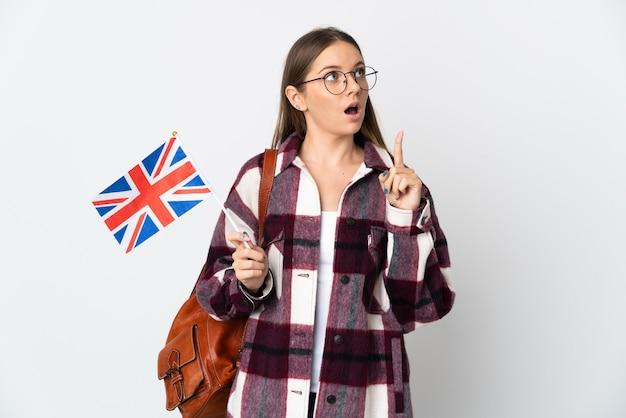 Junge litauische frau, die eine britische flagge lokalisiert auf weißem hintergrund hält, der eine idee denkt, die den finger nach oben zeigt