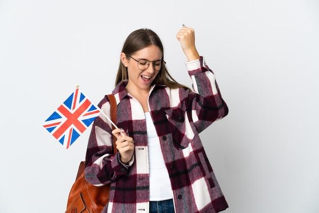 Junge litauische frau, die eine britische flagge lokalisiert auf weißem hintergrund hält, der einen sieg feiert
